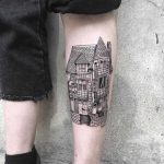 Black house tattoo on the left shin