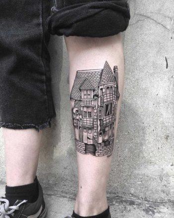 Black house tattoo on the left shin