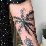 Blackwork palm tree tattoo on the left forearm