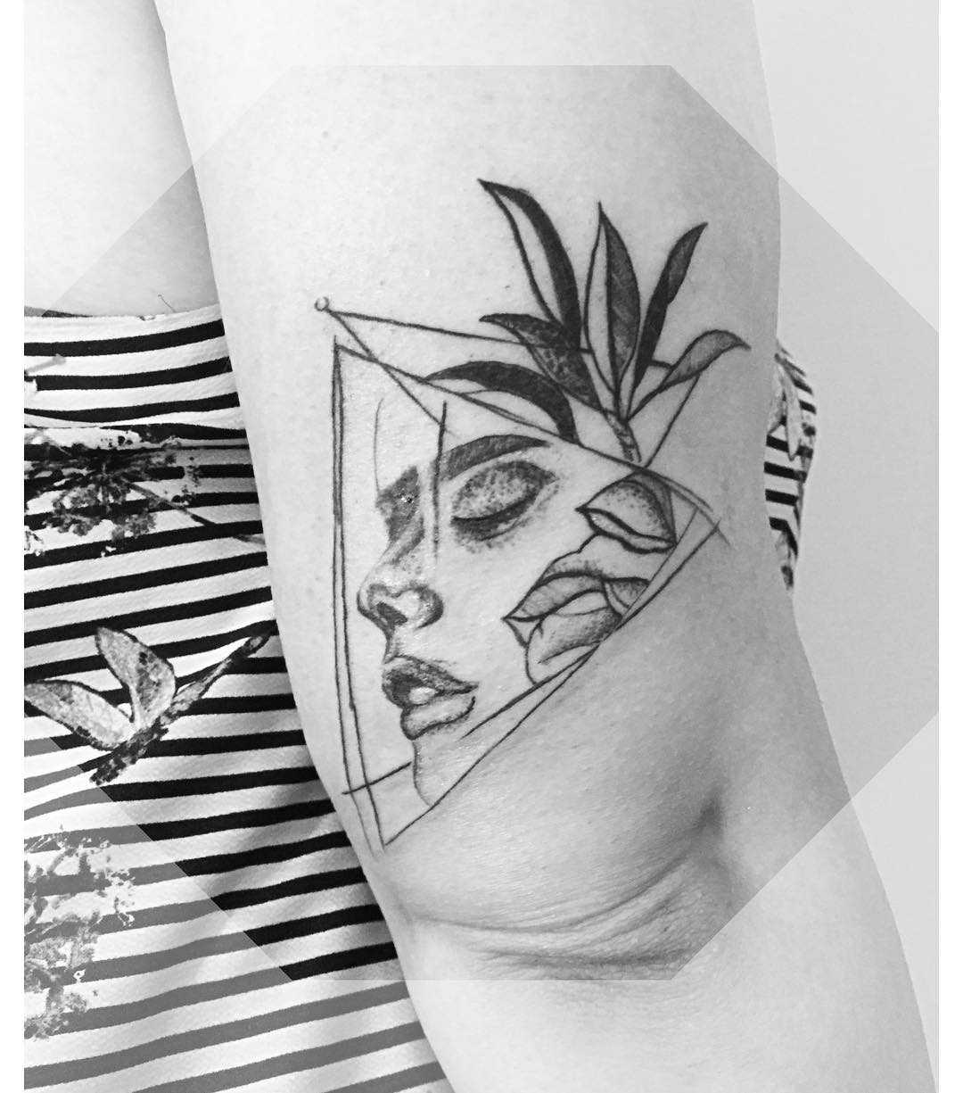 Face within flowers tattoo