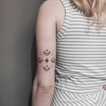 Four moons tattoo on the left arm