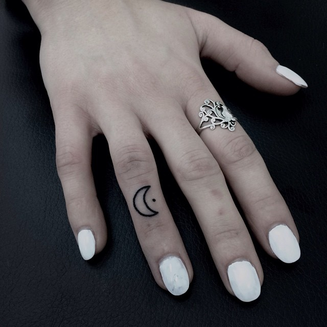 Hand-poked moon tattoo on the ring finger