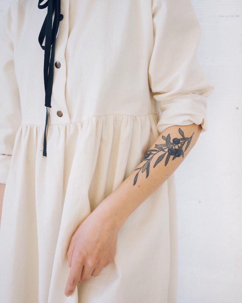 Minimalist olive branch tattoo on the forearm