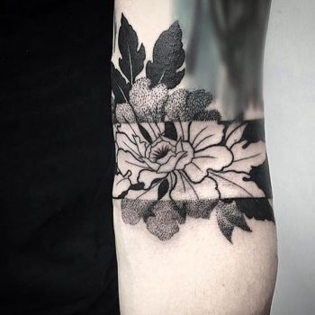 Negative space flower tattoo on the forearm