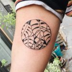 Negative space monstera circle tattoo