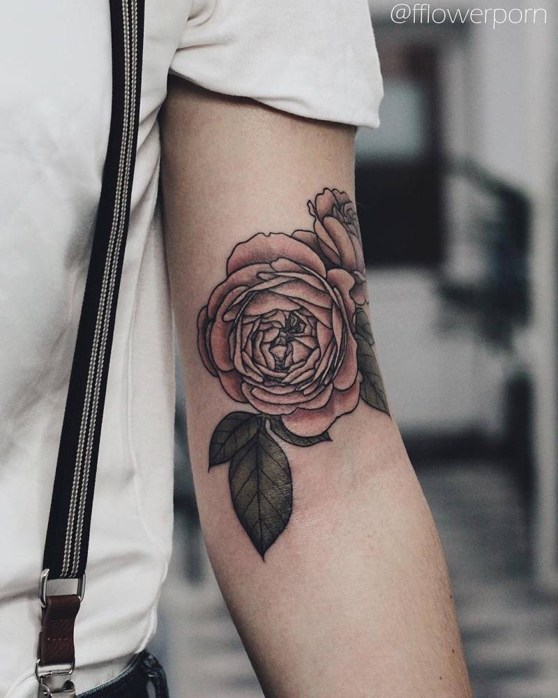 Pink rose tattoo on the left arm