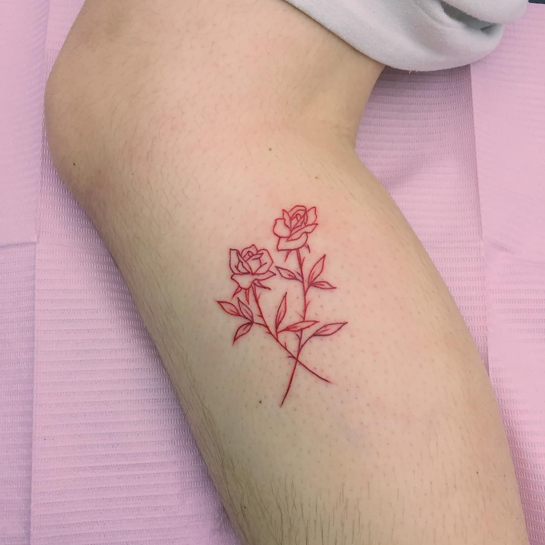 Red crossed roses tattoo