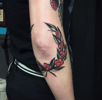 Wreath tattoo around the elbow by Witchwood Tattoo