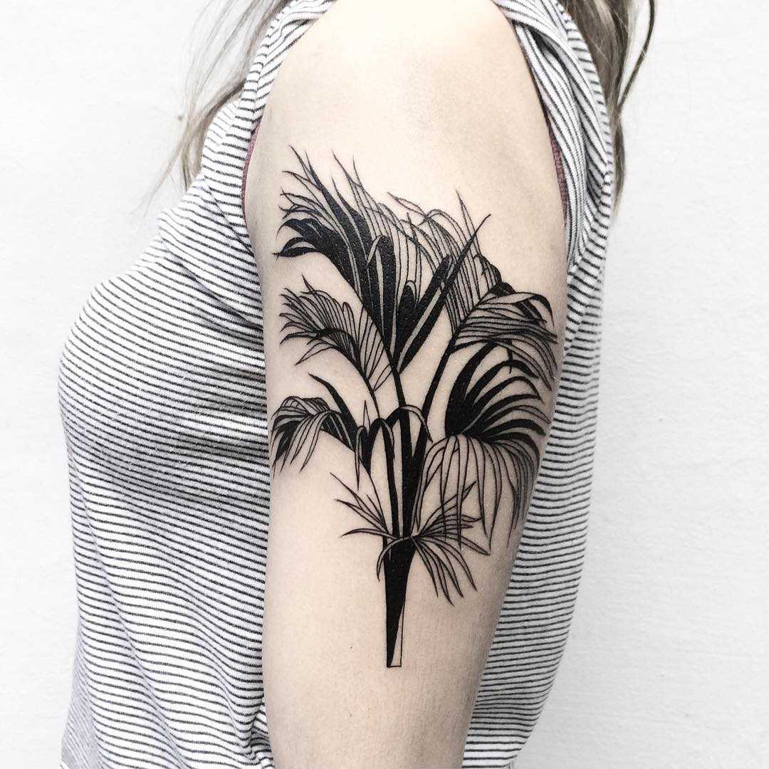 Black branches tattoo on the arm