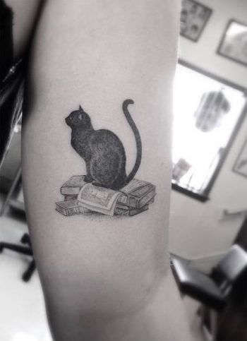 Black cat tattoo on the arm