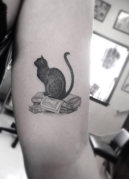 Black cat tattoo on the arm
