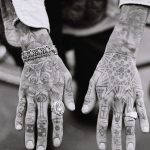 Black tattoos inked all over the hands