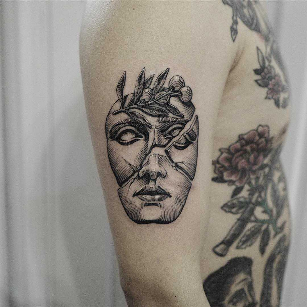 Broken mask tattoo