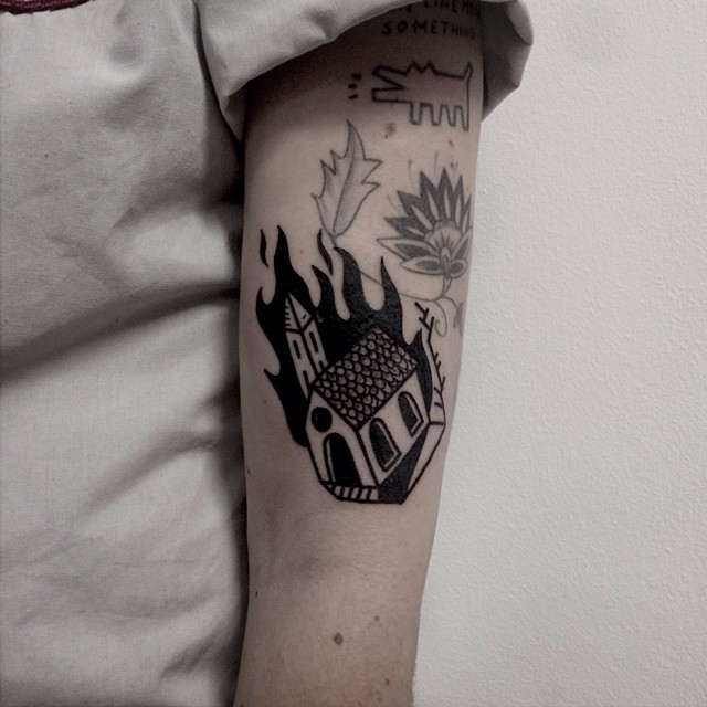 Burning building tattoo on the arm