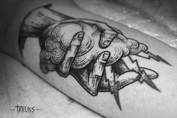 Hand holding a cloud tattoo