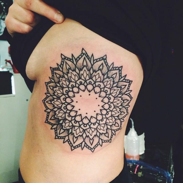Large mandala tattoo on the left rib