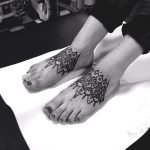 Matching ornament tattoos on both feet