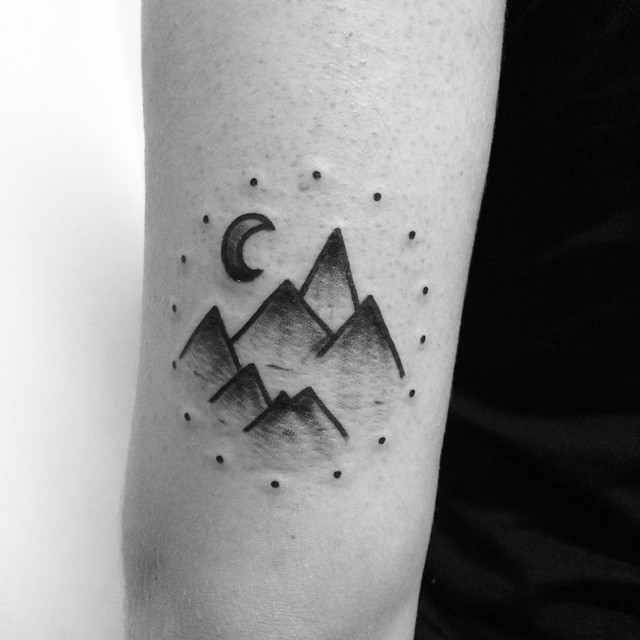 Mountains in a dotted circle tattoo