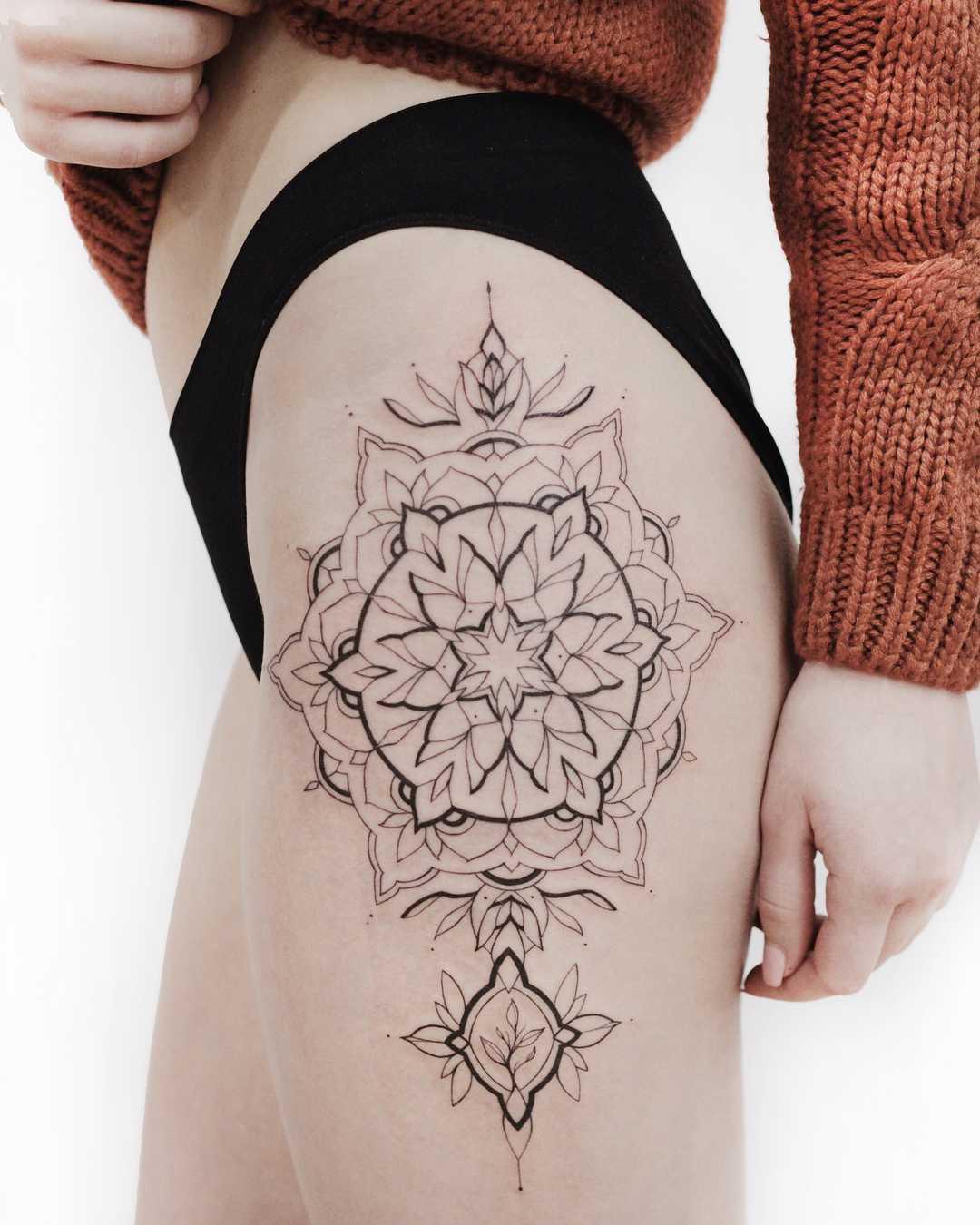 Ornamental mandala tattoo on the left hip