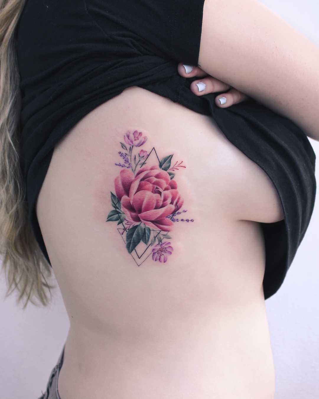 Peony tattoo on the rib cage by Iris Tattoo Art