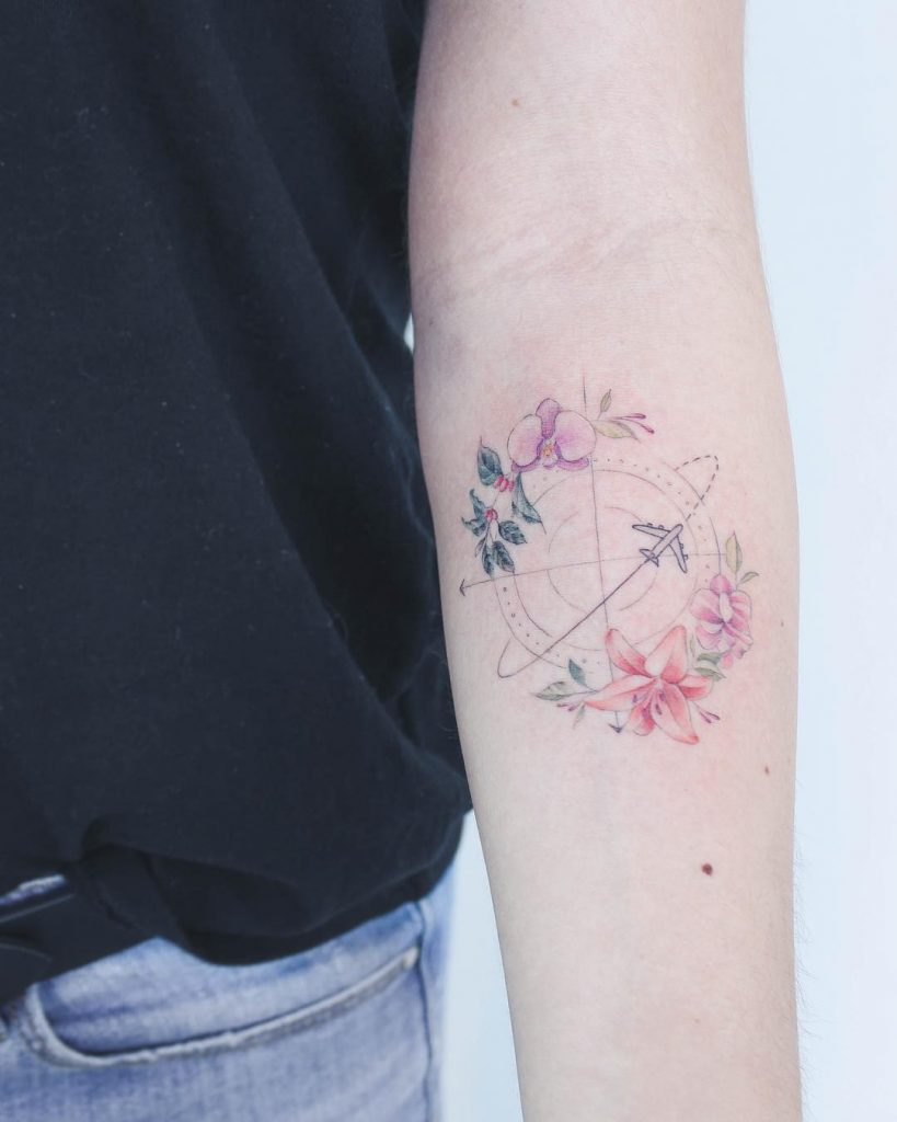 Plane, compass, and flowers tattoo