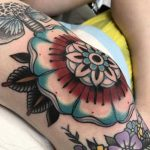 Red and blue mandala tattoo on the knee