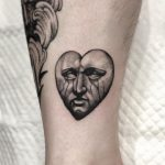 Sad stone face done at Lighthouse Professional Tattoo