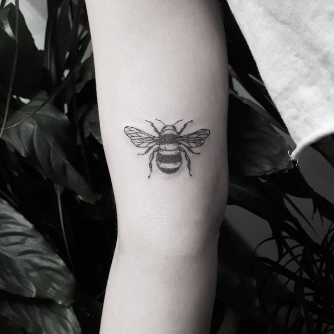Small black and grey bee tattoo