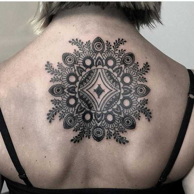 Stylized floral mandala tattoo on the back