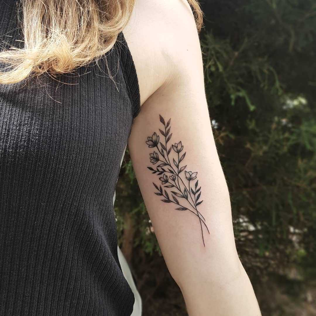 Subtle flowers tattoo on the bicep