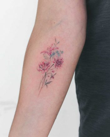 Tattoo of a lily, forget-me-nots, dahlia, peony, and fuchsia