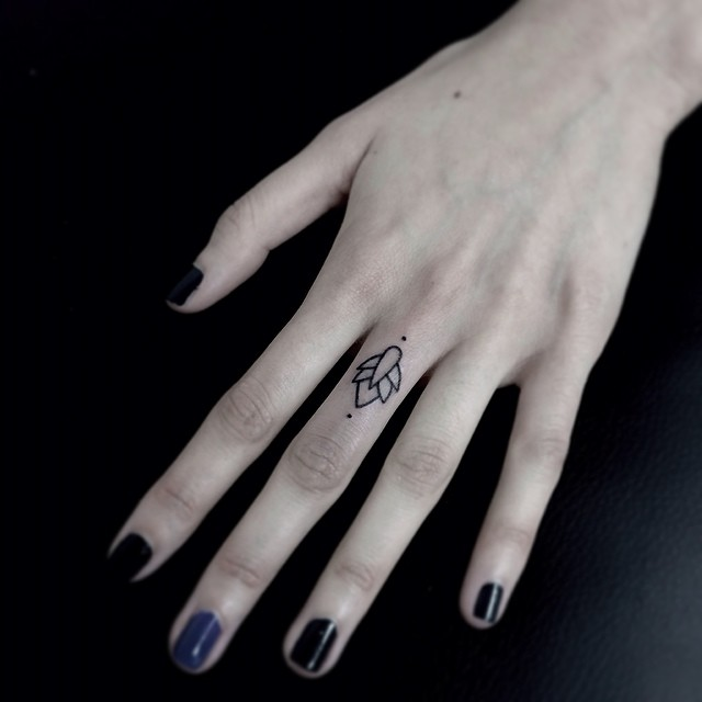 Tiny ornament tattoo on the middle finger