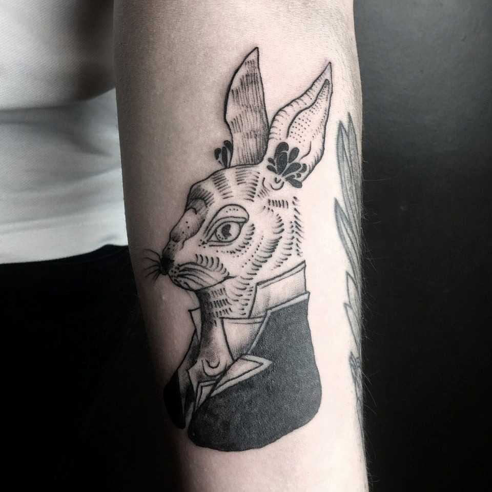 Woodcut rabbit tattoo on the left forearm
