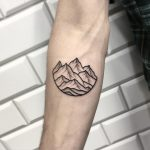 A minimalist mountains landscape tattoo
