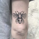 Black and grey bee tattoo on the triceps
