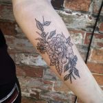Black and grey peony tattoo on the forearm