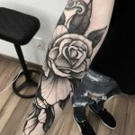 Black and white rose tattoo on the forearm