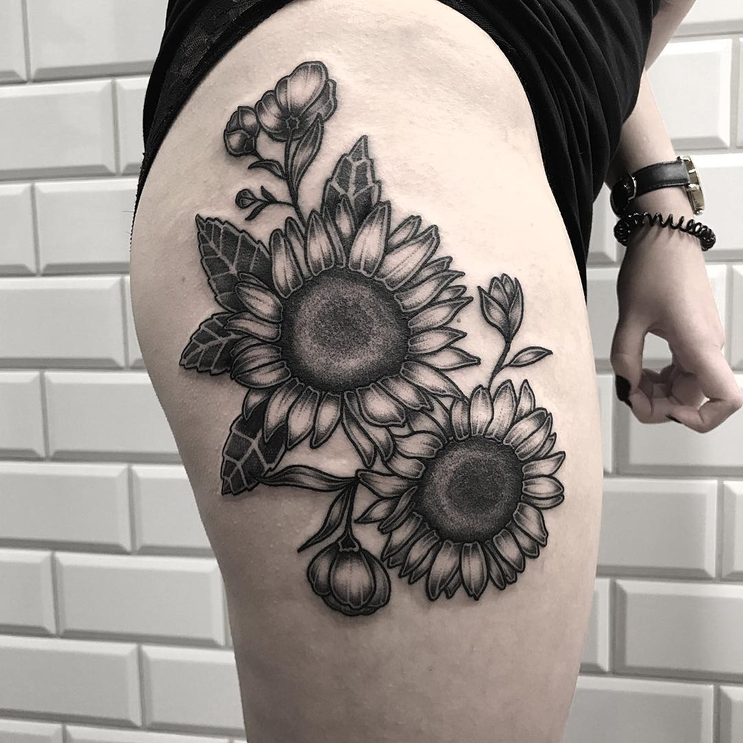 Black sunflower tattoo on the thigh