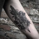 Blackwork rose and dagger tattooed on the arm
