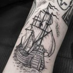 Blackwork ship tattoo on the arm
