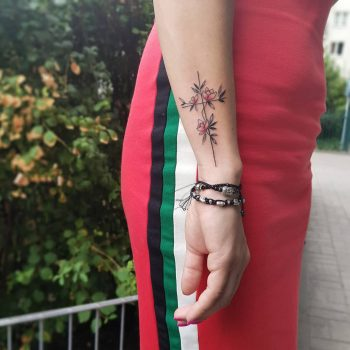 Floral cross tattoo on the wrist