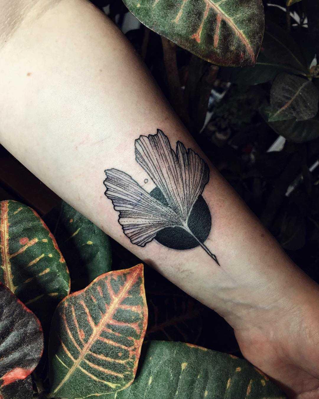Ginkgo leaf and a black circle tattoo
