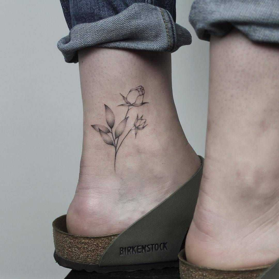 Hand-poked rose tattoo on the inner ankle