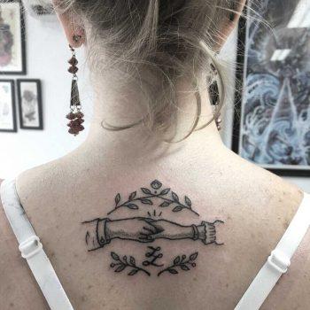 Handshake tattoo on the upper back