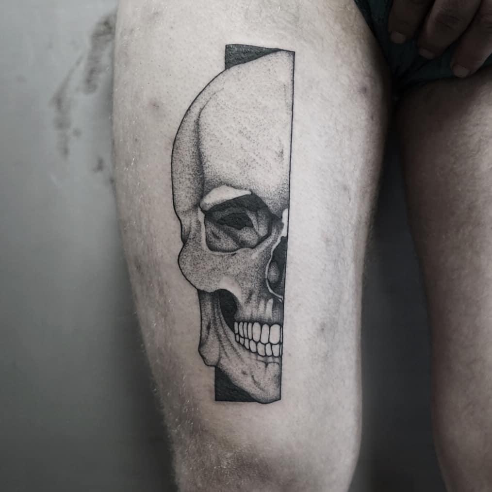 Hyper-realistic half skull tattoo