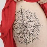 Linear black mandala tattoo on the hip