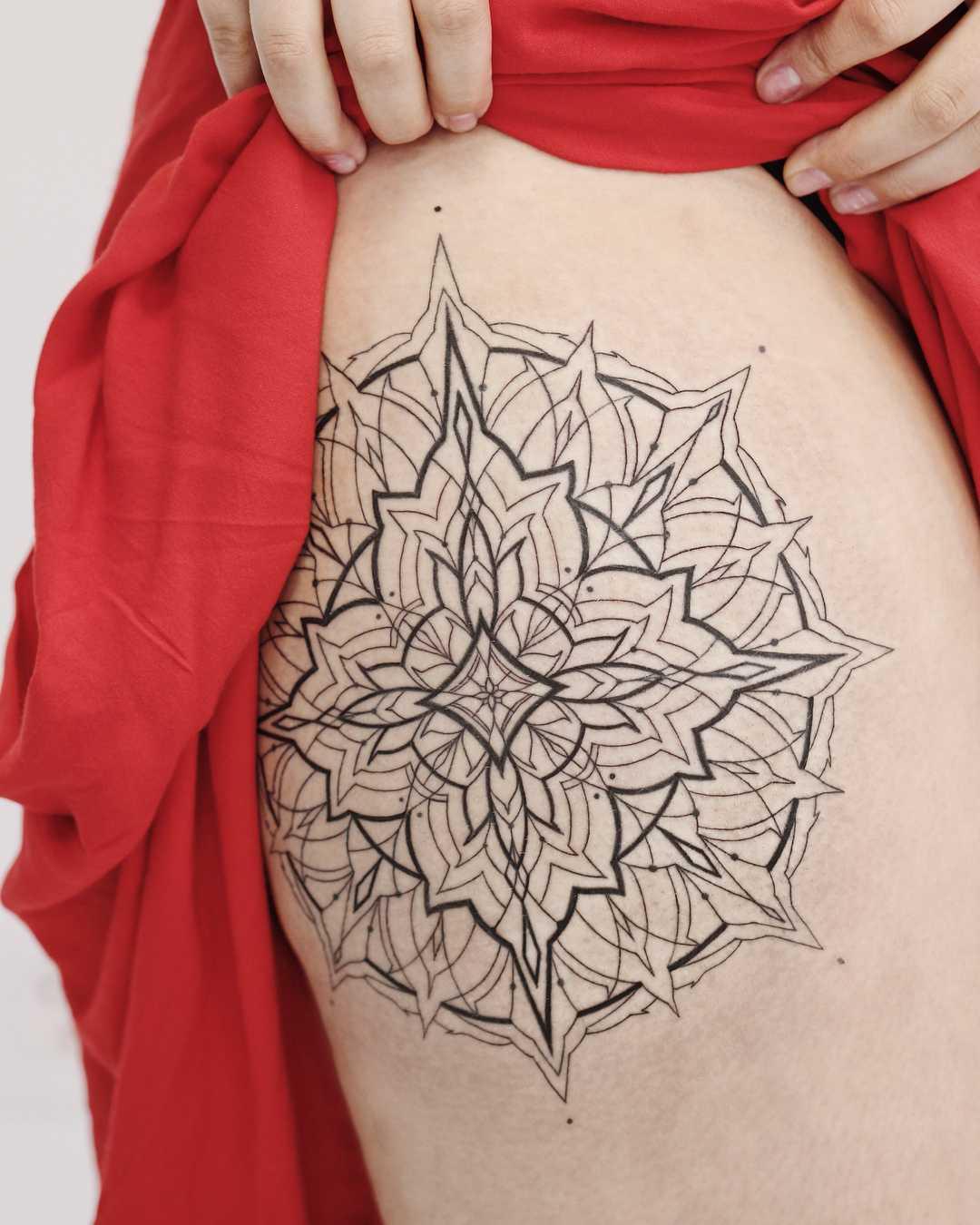 Linear black mandala tattoo on the hip