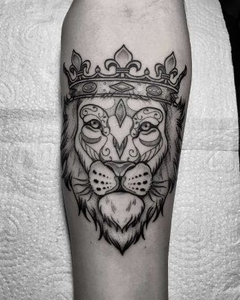 Lion with a crown tattoo