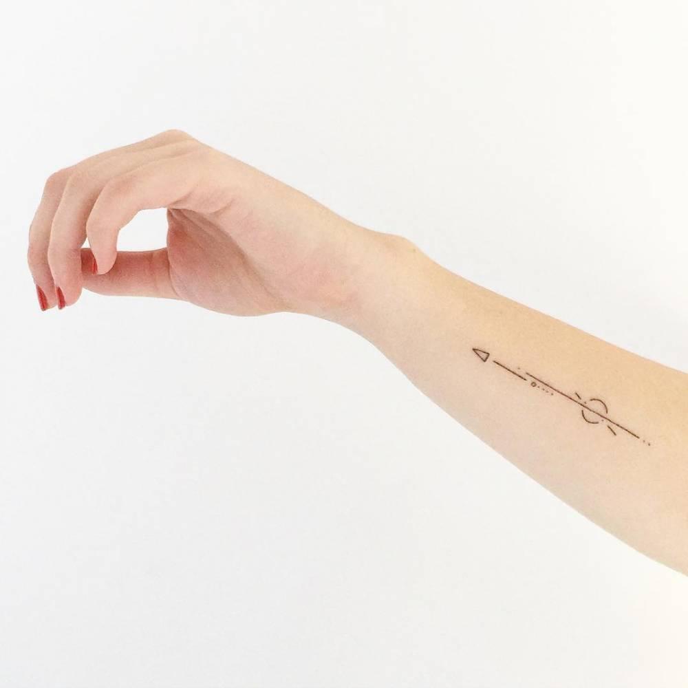 Minimalist arrow tattoo on the forearm