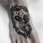 Skull and chain tattoo on the foot